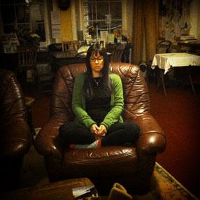 Rachel meditating in a big chair
